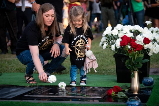 Lisa Baker, widow of Daniel Baker, and their daughter Meredith place carnations on the grave marker during a one-year memorial service for Dickson County Sheriff's Office Sgt. Daniel Baker at Dickson County Memorial Gardens in Burns, Tenn., Thursday, May 30, 2019. Baker was killed in the line of duty on May 30, 2018.
