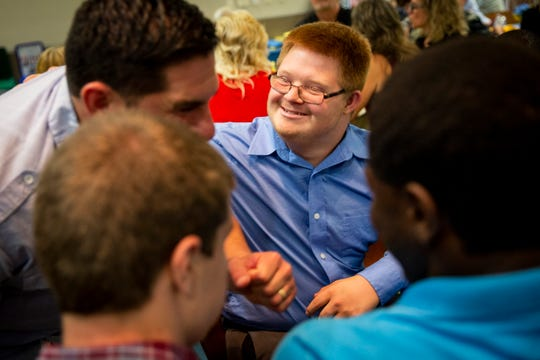Steven Newell, center, smiles as he talks to program director Mike Wexler, left, during the banquet for the Naples High School Career Transition and Experience program at Naples Botanical Garden on Wednesday, May 29, 2019. Steven's mom, Becky Newell, says that the program has helped her son envision his future and has helped him build the skills and independence he needs to reach it.