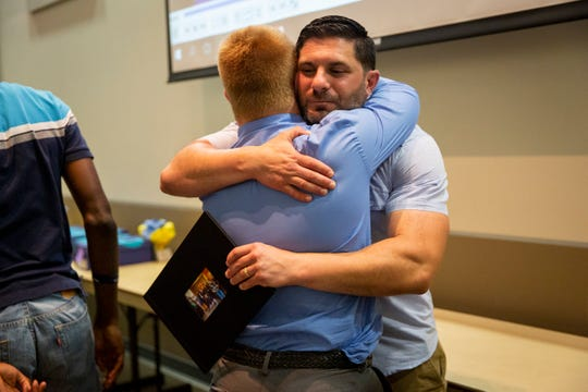 Steven Newell hugs program director Mike Wexler after giving him a thank you gift during the banquet for the Naples High School Career Transition and Experience program at Naples Botanical Garden on Wednesday, May 29, 2019.