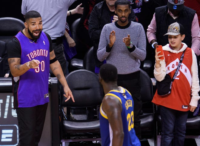 Rapper Drake, left,, says something to Golden State Warriors forward Draymond Green (23) after the Toronto Raptors defeated the Warriors in Game 1 of the NBA Finals, Thursday, May 30, 2019, in Toronto. (Nathan Denette/The Canadian Press via AP)