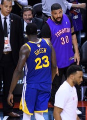 Rapper Drake, right, says something to Golden State Warriors forward Draymond Green (23) after the Toronto Raptors defeated the Warriors in Game 1 of the NBA Finals, Thursday, May 30, 2019, in Toronto. (Nathan Denette/The Canadian Press via AP)