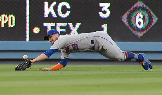 New York Mets left fielder J.D. Davis can't reach a ball hit for a triple by Los Angeles Dodgers' Chris Taylor during the first inning of a baseball game Thursday, May 30, 2019, in Los Angeles. (AP Photo/Mark J. Terrill)