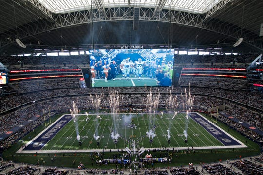 In this Jan. 3, 2016 photo, the Dallas Cowboys jog onto the field at the start of an NFL football game against the Washington Redskins at AT&T Stadium in Arlington, Texas. The first stadium with construction costs that passed the $1 billion price tag, AT&T Stadium opened for the Cowboys for the 2009 season in the suburb of Arlington with a massive, center-hung, high-definition videoboard as the premier attraction among many Texas-sized amenities.