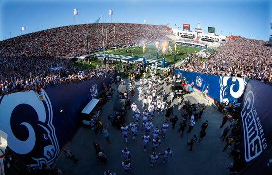 In this Aug. 13, 2016 photo, the Los Angeles Rams take the field at Los Angeles Memorial Coliseum for a preseason NFL football game against the Dallas Cowboys, in Los Angeles. Opened in 1923, the Coliseum first gained the Rams as a tenant in 1946 when they moved west from Cleveland.