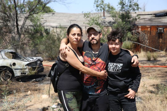 Evelyn Koch and her partner Jack Henley, of Tulorosa, along with their son Jacob, 12, stand in front of their Pontiac Firebird that caught fire Friday, May 31, 2019, while the family traveled west on US 70 near Organ.