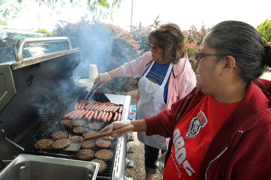 Lulu Hampton, left, and Rose Warren, right, help prepare the hot dogs and hamburgers on May 27 for the Bloomfield School District Summer Meal Program kick off barbecue at Salmon Park.