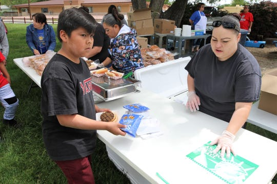 Jeremiah Martinez, left, receives part of his lunch from Alicia Chavez, right, on May 27 during the Bloomfield School District Summer Meal Program kick off barbecue at Salmon Park.
