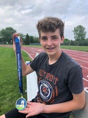 Josh Lassaline shows the medal he received after running in the 2019 Bayshore Marathon, where he was the youngest runner. The eighth grader also runs track and cross country at Millennium Middle School in South Lyon.