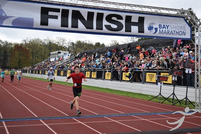 Josh Lassaline, 14, of South Lyon, crosses the finish line at the Bayshore Marathon on May 25, 2019. Lassaline was the youngest runner in the race.