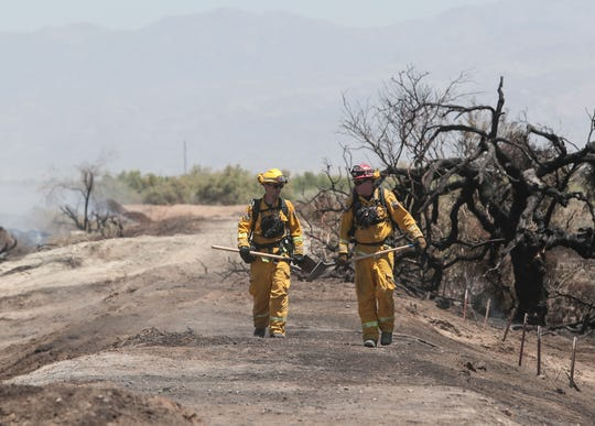 Firefighters work the fire near Avenue 66 and Fillmore Street in Thermal where dozens of acres of green waste were burning, May 31, 2019.