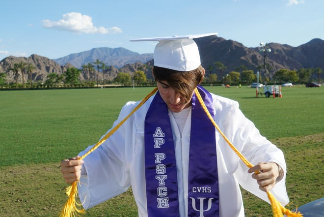 Coachella Valley High School valedictorian Eric Arias adjusts his honor cord and sashes before heading into graduation at the Indian Wells Tennis Garden, Indian Wells, Calif., May 29, 2019.