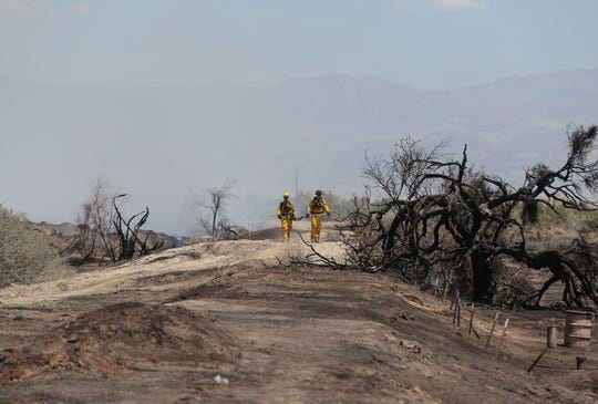 Firefighters work a fire near Avenue 66 and Fillmore Street in Thermal where dozens of acres of green waste were burning, May 31, 2019.