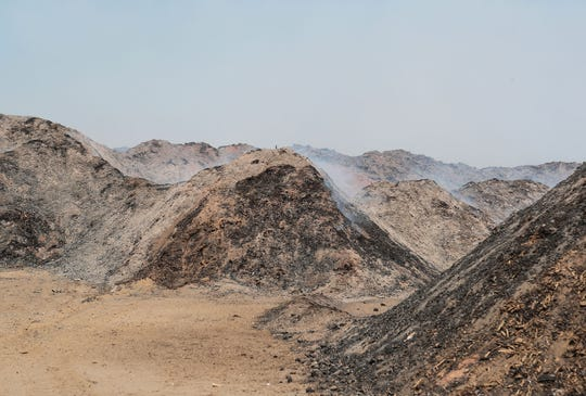 Dozens of acres of green waste smolder at a garbage business in the 66 Fire in Thermal, May 31, 2019.
