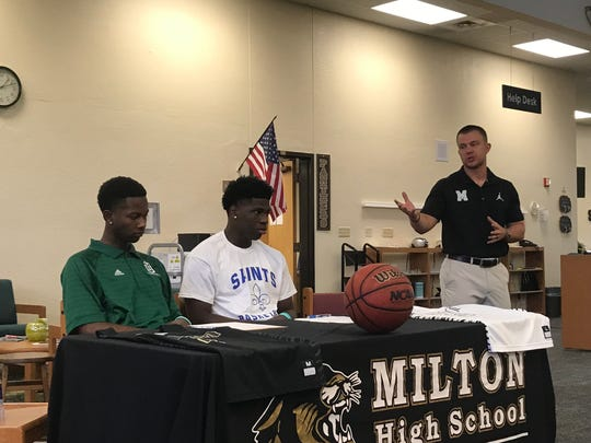 Milton basketball coach Joey Murdock celebrates Tristan Harris ( far left) and Tobias Daniels. Milton basketball's culture has had a major turnaround.