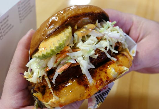 Fried chicken sandwich with southern slaw, pickles and 'kick-it-up' sauce on a brioche bun at Monroe's Hot Chicken in Phoenix, AZ.