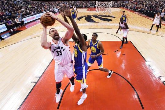 Marc Gasol #33 de Toronto Raptors intenta encestar el balón ante el acoso de la defensiva californiana.