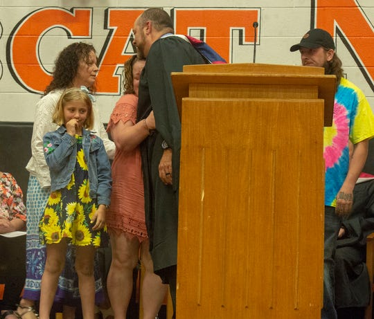 Northeastern principal Mathew Gay hugs the mother of Masey Dacheux, who was killed in a car crash Jan. 31. Dacheux's family received her diploma at Northeastern's graduation on Thursday, May 30, 2019.