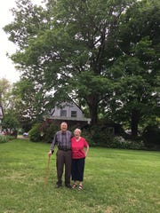 John and Annabelle Wenzke in the backyard of their home with the towering red oak tree behind them.