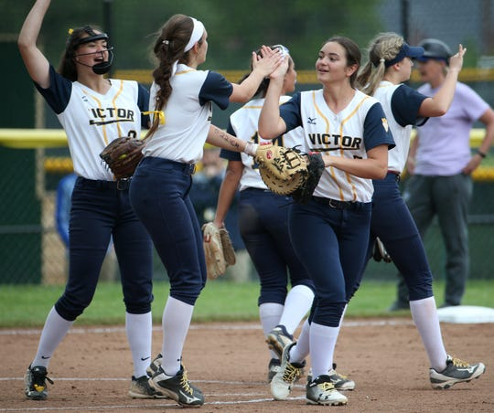 Victor celebrates its second out in the fourth inning against Webster Schroeder in the Section V Class AA softball semifinals in Brockport.