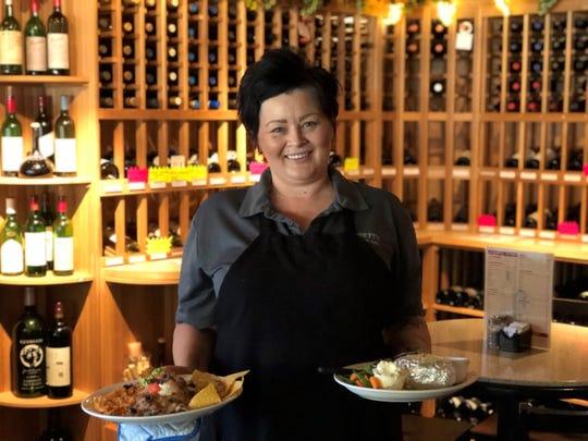 Assistant Manager Dana Laughlin serves dinner at Corbett's Restaurant in downtown Redding, something new since February.