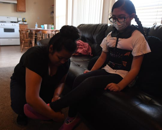 Priscilla Ayala puts her daughter's slippers on so she can go outside. Honesty can't bend at the waist after doctors implanted a rod in her spine. May 31, 2019.