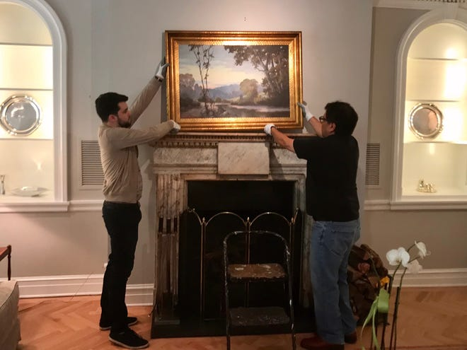 Taylor Velarde (left) and Mario Castillo (right) hang a painting above a fireplace in the European Union residence on May 15, 2019. The art is on loan to the EU from the San Angelo Museum of Fine Arts.