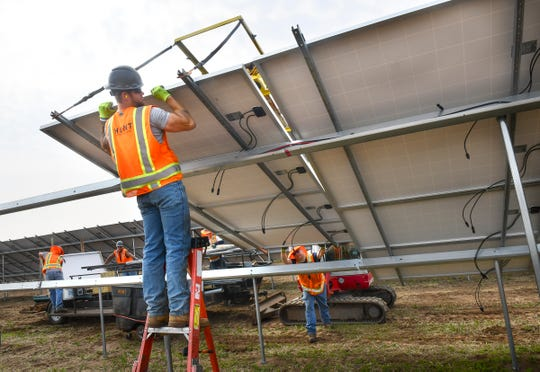 Crews position panels Thursday, May 30, in a new solar garden along Sherburne County Road 8 south and east of St. Cloud.