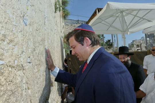 Gov. Ron DeSantis prays at the Western Wall in the Old City of Jerusalem in May. A common tradition is to insert handwritten notes and prayers into the cracks along the wall. The governor inserted his own plea to spare Florida from hurricanes this season.