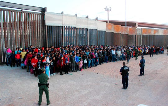 This May 29, 2019, photo released by U.S. Customs and Border Protection shows some of the 1,036 migrants who crossed the U.S.-Mexico border in El Paso, the largest group that the Border Patrol says it has ever encountered. Video shows them going under a chain-link fence to the U.S., where they waited for agents to arrive. The Border Patrol has encountered 180 groups of more than 100 people since October, compared with 13 during the previous 12-month period and two the year before.