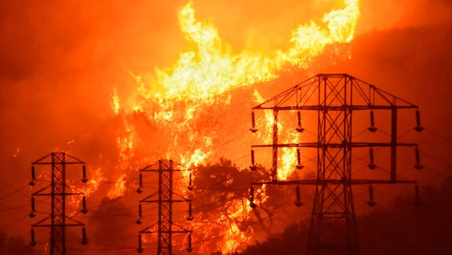 This Dec. 16, 2017, file photo provided by the Santa Barbara County Fire Department shows flames burning near power lines in Montecito.