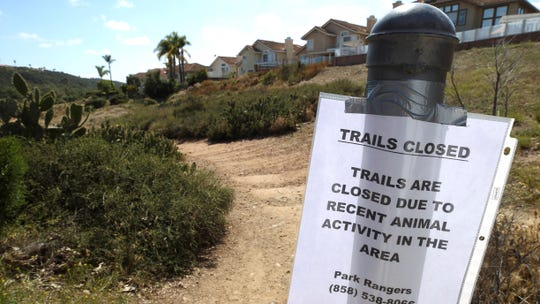 In this photo from earlier this week, a sign is posted at a trailhead to the Los Penasquitos Canyon Preserve after an animal attack in San Diego.