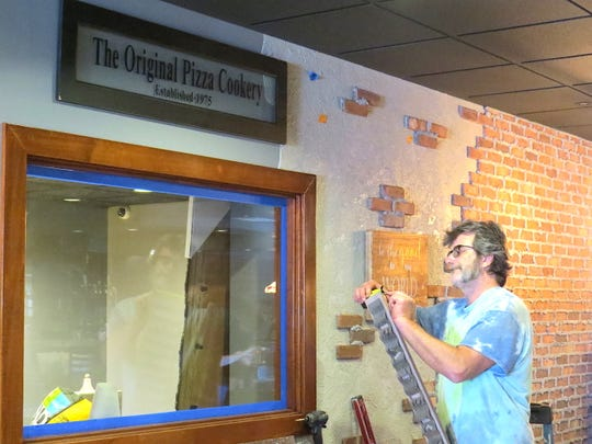 Carpenter Loren Davidson, of Woodland Hills, prepares to hang artwork at The Original Pizza Cookery in Thousand Oaks. The restaurant's Nostalgia Room, visible through the window, will be filled with furniture and other mementos from the Woodland Hills location.