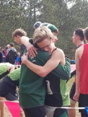 Running helped strengthen the friendship between Isaiah Winowiski and Herbie Richardson, hugging here at the end of the cross country race.