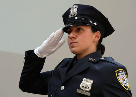 Harrison Police Officer Alexandra Menniti salutes as she takes the stage for her certificate at the 147th Westchester County Police Academy graduation ceremony at Westchester Community College May 31, 2019 in Valhalla.