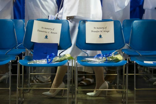 Chairs for Dametrius Benson and Brandon Wingo sit in the front row of Howard High School of Technology's graduation ceremony Thursday, May 30, 2019 at the Bob Carpenter Center. Both Wingo Benson were killed by gunfire in Wilmington.