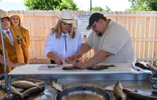 Sara Cox gets some tips from Tom Lang of the Texas Parks and Wildlife Department as they demonstrate the new fish cleaning station near the Lake Wichita boat ramp Friday. The facility offers cutting boards, a stainless steel sink, spray nozzles, electricity and a grinder to easily dispose of fish carcasses after fileting.