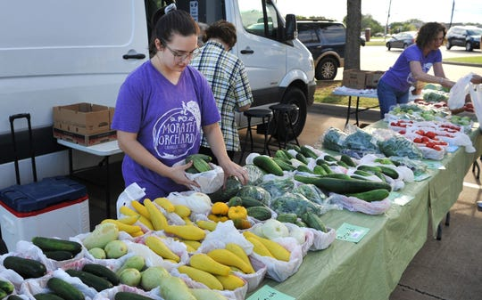 Morath Orchard volunteer Caroline King helps stock fresh goods for the Farmer's Market at Hospice Friday morning.