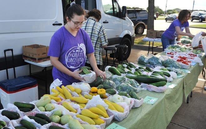 Morath Orchard volunteer Caroline King helps stock fresh goods for the Farmer's Market at Hospice Friday morning.