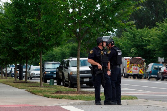 Virginia Beach Police Officers huddle near the intersection of Princess Anne Road and Nimmo Parkway following a shooting at the Virginia Beach Municipal Center on Friday, May 31, 2019 in Virginia Beach, Va, At least one shooter wounded multiple people at a municipal center in Virginia Beach on Friday, according to police, who said a suspect has been taken into custody. (Kaitlin McKeown/The Virginian-Pilot via AP) ORG XMIT: VANOV102