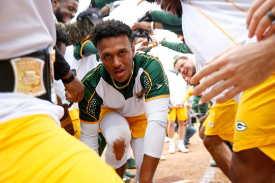 Packers quarterback DeShone Kizer is greeted by teammates after hitting a home run in the Green & Gold Charity Softball Game on June 1 at Fox Cities Stadium in Grand Chute.