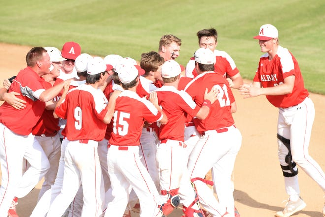 The Albany baseball team surrounds Jackson Chapman (10) after his walk-off sacrifice fly to beat New Deal 4-3 on Friday, May 31, 2019. The victory completed the Region I-2A final series comeback as Albany won its second Region I-2A title in the last three years.