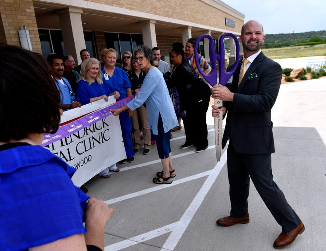 Brad Holland, the president and CEO of Hendrick Health System, holds an oversized pair of scissors, waiting for more to join him, at the May 24 dedication of the Hendrick Medical Plaza in Brownwood. The new clinic will serve between 1,800 - 2,000 patients a month.
