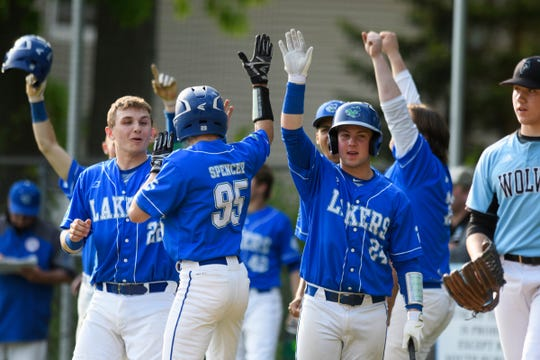 Colchester's Will Spencer (95) high fives Lucas McClanahan (22) and Brody Stannard (24) as he crosses the plate for a run during the baseball quarterfinal game between the Colchester Lakers and the South Burlington Wolves at South Burlington High School on Friday afternoon May 31, 2019 in South Burlington, Vermont.  (BRIAN JENKINS/for the FREE PRESS)
