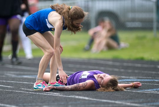 Lamoille's MegAnne Gilmore, left, checks on runner-up Abby Broadley of Bellows Falls after the pair finished the 3,000 meters during the Division II state championship meet at South Burlington High School on Saturday, June 1, 2019.