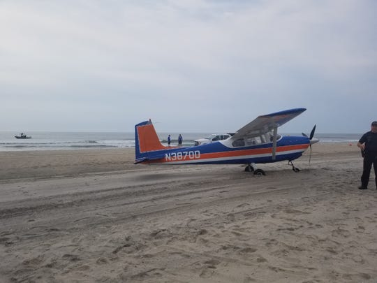 A small plane sits on the beach after an emergency landing in Ocean City on Saturday morning.