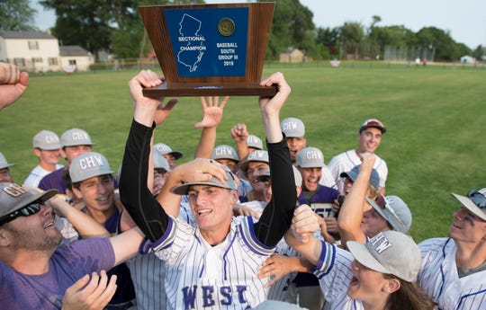 Cherry Hill West's Scott Shaw hoists the trophy and celebrates with teammates after Cherry Hill West defeated Triton, 6-3, in the South Jersey Group 3 baseball final played at Triton High School in Runnemede on Friday, May 31, 2019.