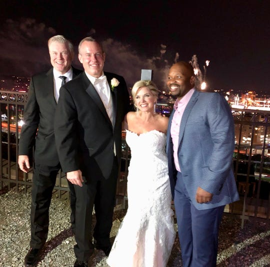 Mike Dardis and Sheree Paolello (center) celebrated their marriage Friday evening in Mount Adams, alongside others from the WLWT News team: Meteorologist Kevin Robinson (right) and George Vogel, who reports on sports. The fireworks from Great American Ball Park were an added bonus, Dardis said.