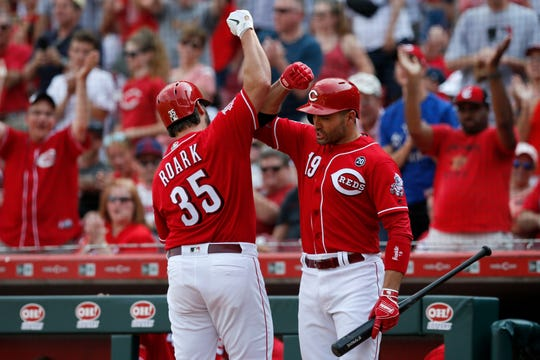 Cincinnati Reds starting pitcher Tanner Roark (35) celebrates with first baseman Joey Votto (19) after hitting a solo home run in the fourth inning of the MLB National League game between the Cincinnati Reds and the Washington Nationals at Great American Ball Park in downtown Cincinnati on Saturday, June 1, 2019. The Reds lost 5-2.