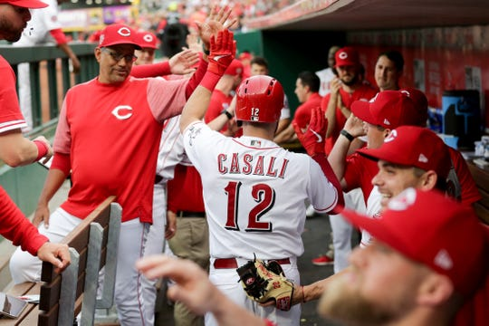 Cincinnati Reds catcher Curt Casali (12) is congratulated in the dugout after hitting a three-run home run in the first inning of an MLB baseball game against the Washington Nationals, Friday, May 31, 2019, at Great American Ball Park in Cincinnati.
