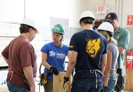 Habitat for Humanities workers with volunteers at a work site.